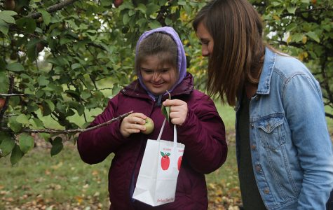After picking an apple at Cider Hill Family Orchard on Thursday, Oct. 11, junior Maria McElwee and senior Madi Reishus admire their find.