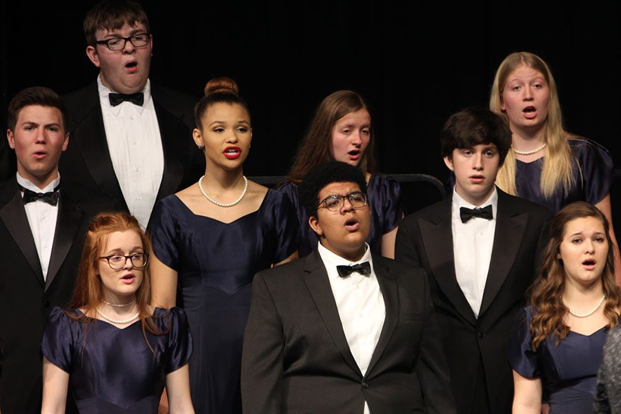 """On stage in the theatre, Jag Singers prepare to sing """"Safe With Me"""" by Bryan Sharpe."""