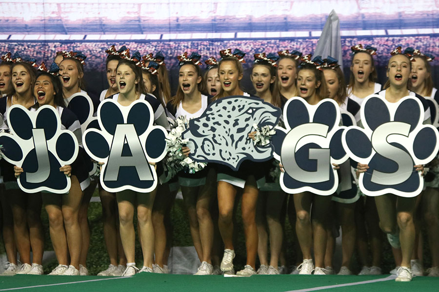 Preparing+to+start+their+crowd+leading+routine%2C+the+cheer+team+yells+while+holding+signs.