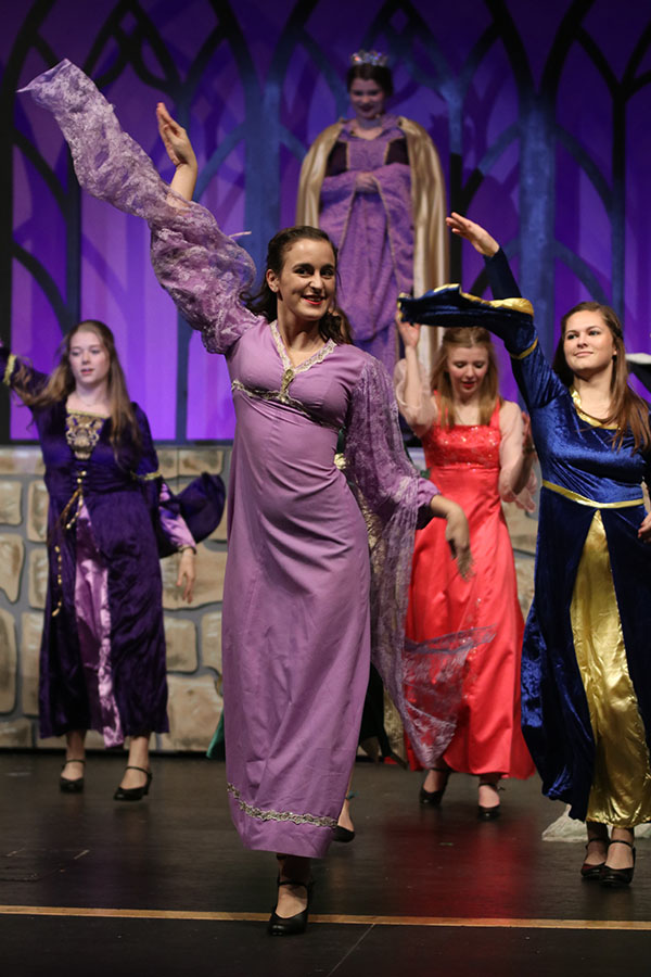 With+her+arms+held+up+high%2C+senior+Josie+Hayes+dances+in+a+scene+with+other+princesses.+