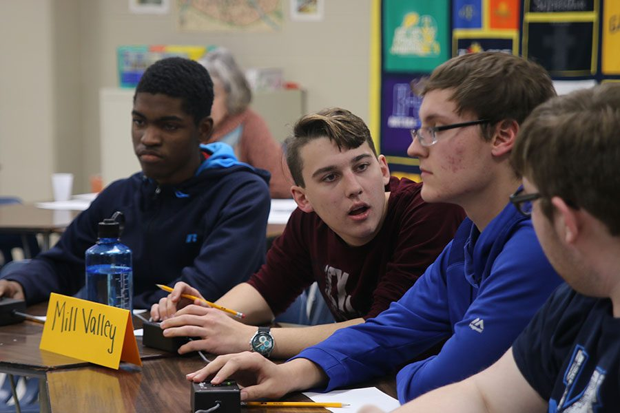 Getting ready to press the buzzer, senior Johannes Seberger discusses to the team about an answer at the Saint Thomas Aquinas tournament on Thursday, Nov. 15.