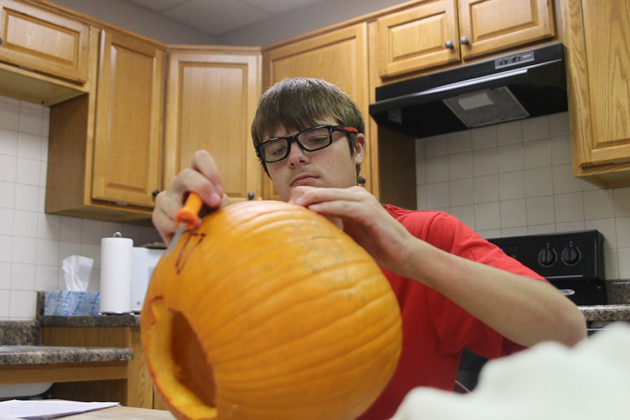 Looking+down+at+his+emptied+pumpkin%2C+Bridge+student+Kyle+Ray+prepares+for+Halloween+festivities+by+carving+a+face+into+the+pumpkin+at+the+Bridge+on+Wednesday%2C+Oct.+31.+++%0A