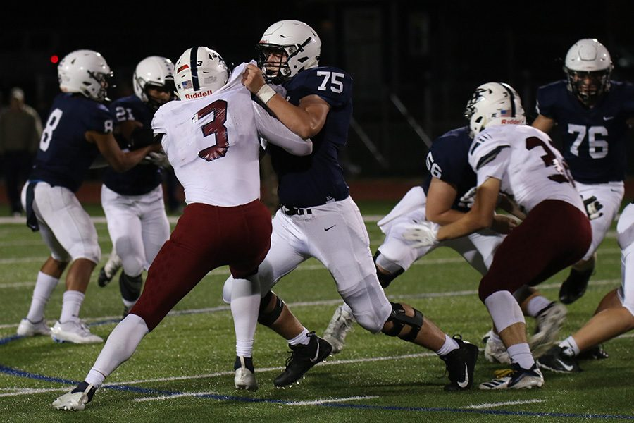 Face to face, sophomore offensive lineman Sam Hecht blocks an opponent from advancing.