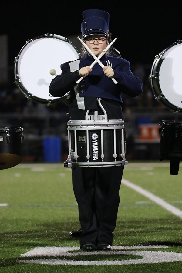 In the middle of the set, junior Abby Lee makes an X with her drumsticks as a visual element to the band's performance.