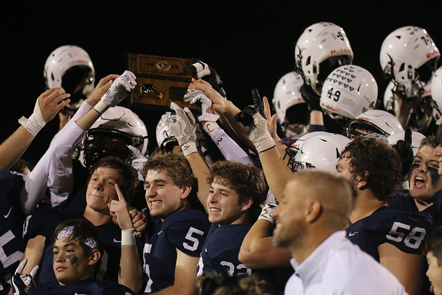 Raising their helmets in the air, the team celebrates the win with the regional trophy.