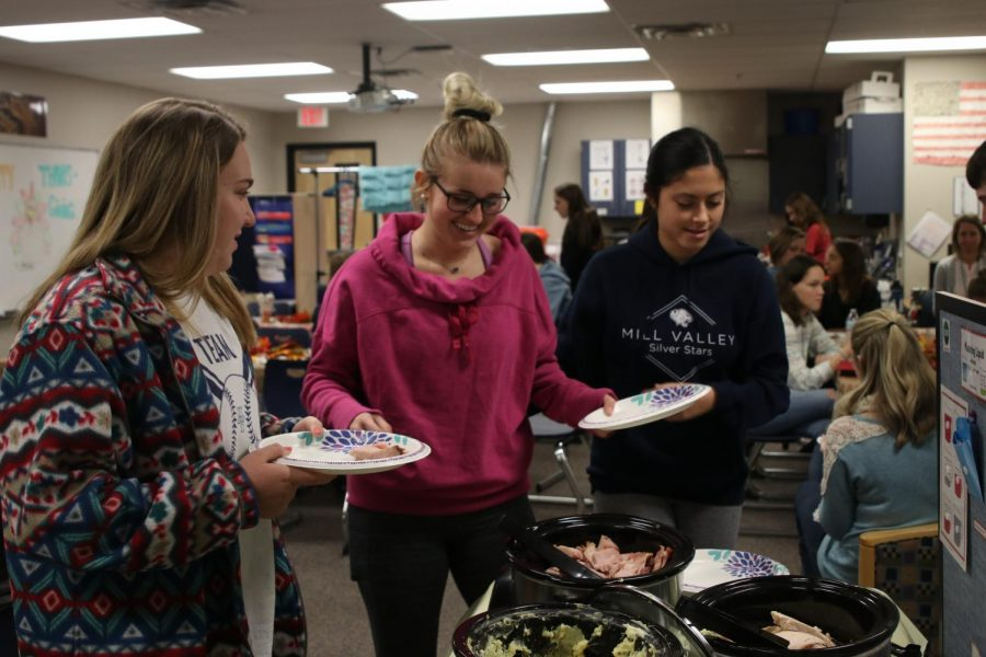 "During the Peers in Learning Thanksgiving meal on Tuesday, Nov. 20, junior Paige Oliver peers over the crockpots of food. ""My favorite part [of the Peers Thanksgiving] is to celebrate with all of the peers and having great food,"" Oliver said. ""I love being in Peers in Learning because, no matter what, my peers always find a way to put me in a good mood. Working with the students makes me feel good that I'm helping [out in our community]."""
