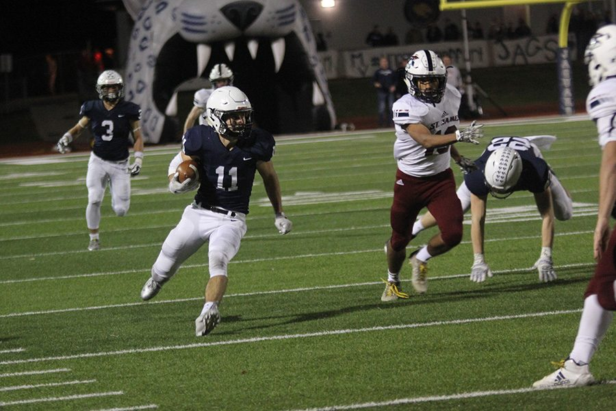 After intercepting the ball, senior defensive back Ben Hanson cuts through members of the opposing team.