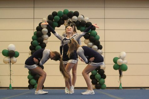 Striking a pose, junior Trinity Ouellette and her stunt group begin their routine.