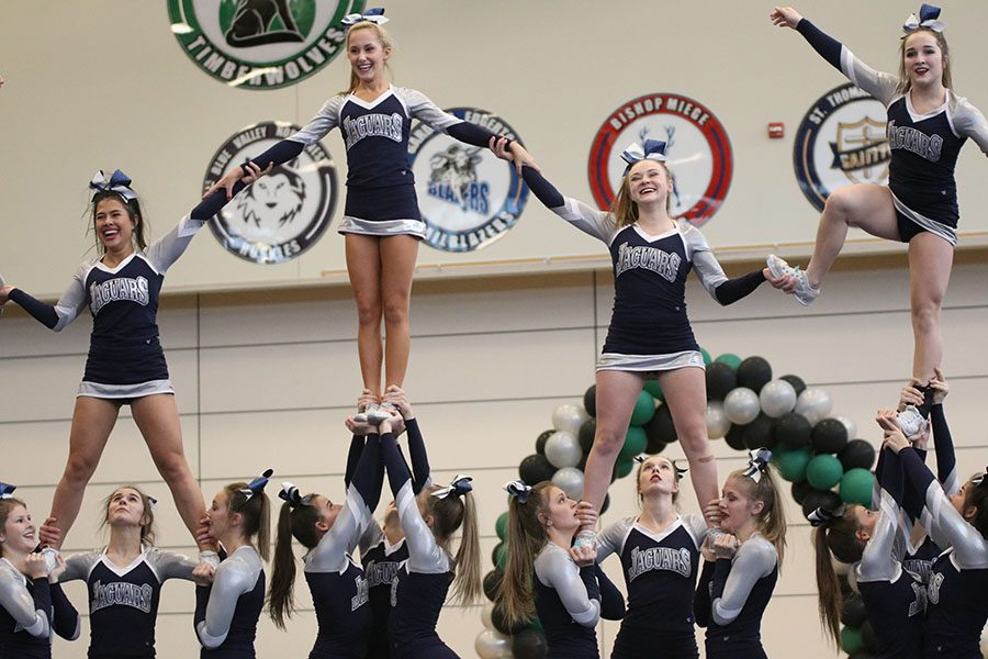 Finishing their routine, the cheer squad smiles as they complete their stunt pyramid.