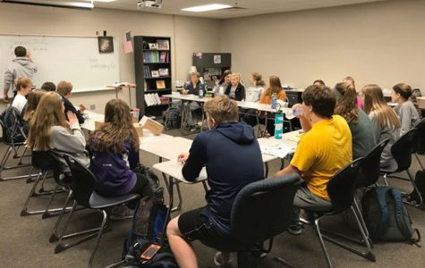 """Members of Fellowship of Christian Athletes sit in a collection of desks as they wait for the morning meeting to begin. """"The purpose of FCA is to unite athletes who are also christians. Sports tie into Christ so we can relate to each other about the same things,"""" junior Morgan Koca said."""