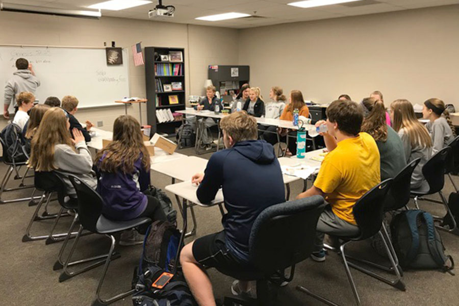 "Members of Fellowship of Christian Athletes sit in a collection of desks as they wait for the morning meeting to begin. ""The purpose of FCA is to unite athletes who are also christians. Sports tie into Christ so we can relate to each other about the same things,"" junior Morgan Koca said."