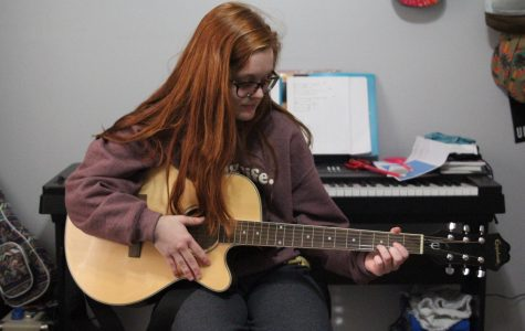 "Strumming her guitar, junior Meghan Sherman practices the song ""Make You Feel My Love"" for her 'The Voice' audition."