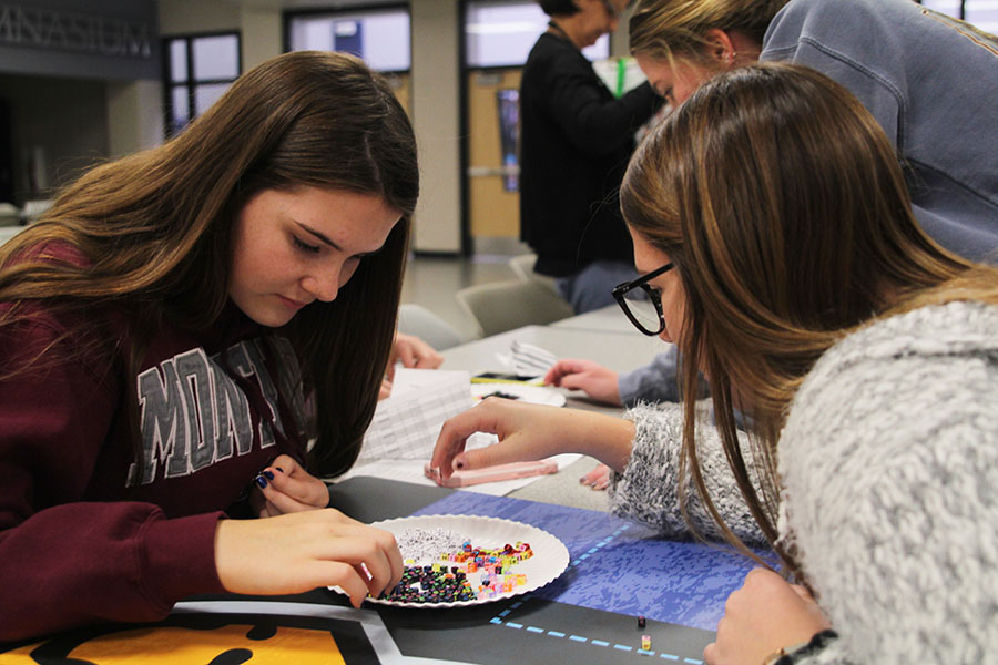 """Sitting in the commons, sophomores Morgan Prosser and Emma Hookstra search for beads to make their bracelets with. JagPRIDE held a stress free seminar on Wednesday, December 5th. """"I went to make bracelets to forget about the stress of finals, spend time with my best friends, and to do something mentally stimulating that wasn't overwhelming."""" said Prosser."""