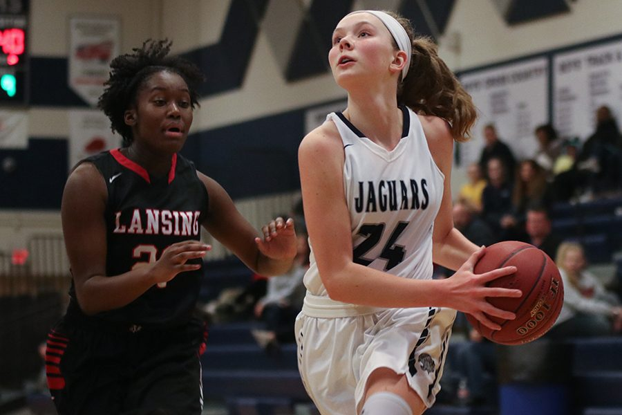 After+making+a+move+around+a+Lansing+player%2C+freshman+Emree+Zars+prepares+to+shoot+the+ball.+Girls+basketball+played+Lansing+High+School+at+home+on+Tuesday%2C+Jan.+15%2C+winning++59-48.