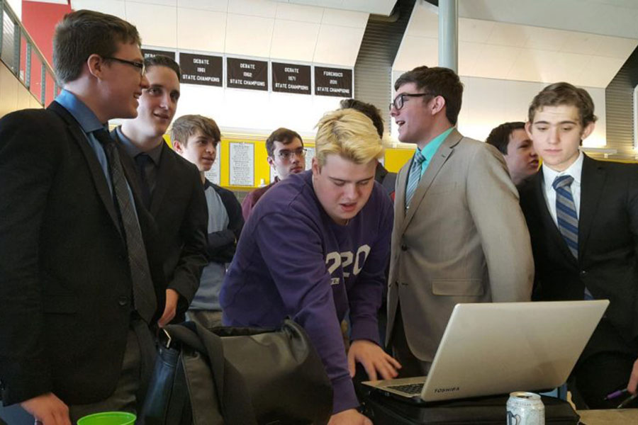 As he pulls up documents on the laptop, Debate assistant coach and alumni Jack Booth helps the team prepare for the second round.