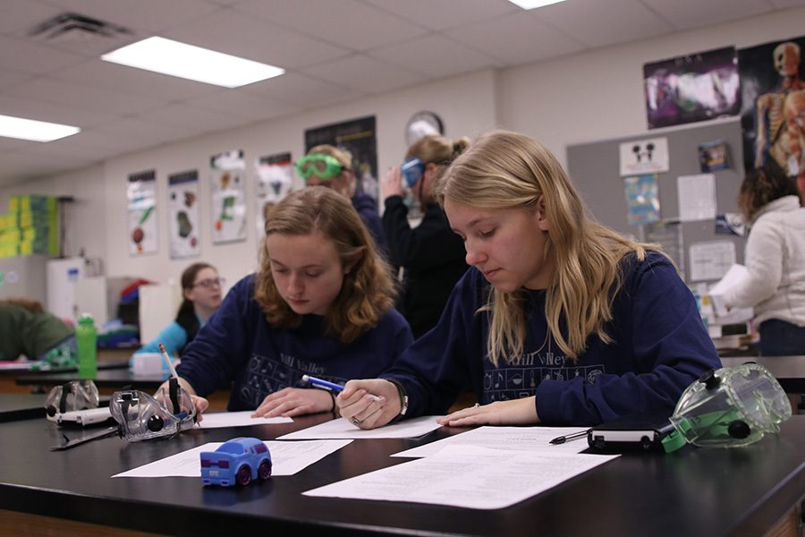 While competing in the experimental design event, senior Sydney Clarkin and junior Callie Roberts begin to write on their papers.