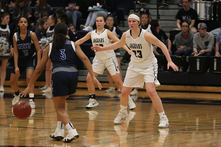 Playing defense in the final quarter, senior Claire Kaifes tries to keep an Olathe West player from getting to the basket.