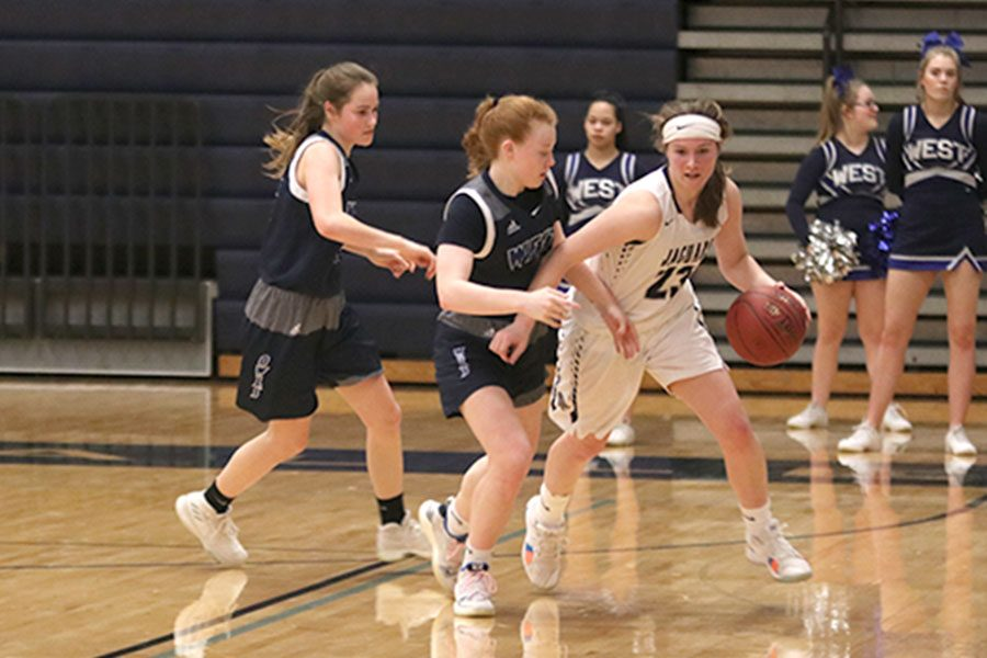 Getting double teamed by two Olathe West players, senior Clair Kaifes tries to find a way to get down court.