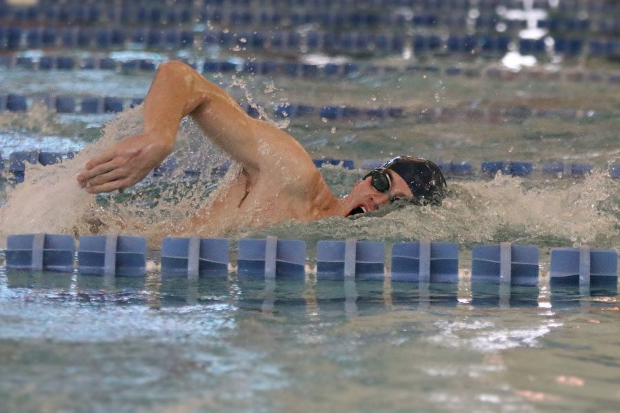 Using his arm to propel him forward, senior Chris Sprenger swims during the 400 yard freestyle relay during the state competition on Friday, Feb. 15.