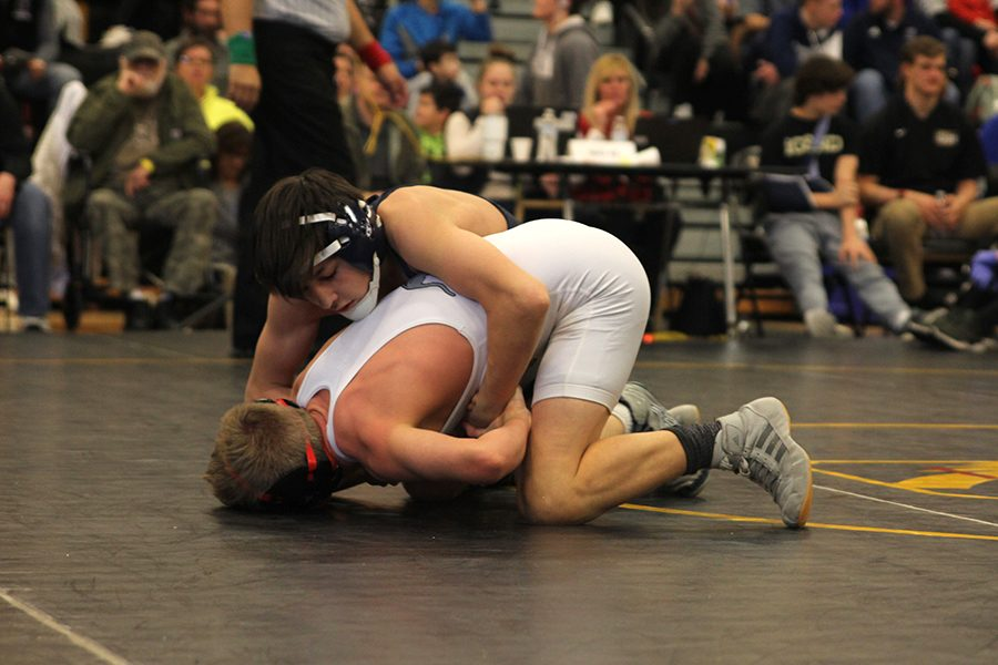 Holding+opponent+down%2C+sophomore+Liam+Sutton+locks+his+arms+around+a+Olathe+West+wrestler.
