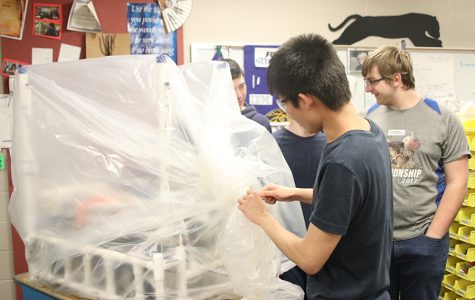 Attaching a zip tie in order to finish bagging the robot, junior Kevin Lee helps his team complete their building process for the season.