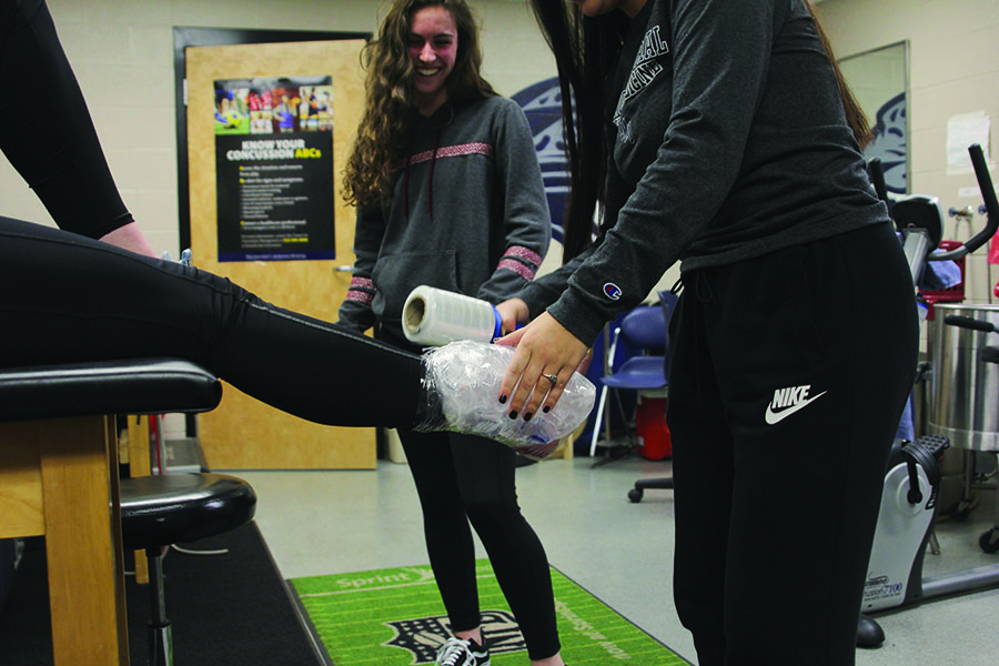 """Student trainers junior Maddie Valencia and sophomore Katie Turner wrap blank Claire Kaifes foot in ice on Tuesday, Jan. 22, """"We see a lot of tendonitis, concussions, ankle sprains"""" said Valencia."""