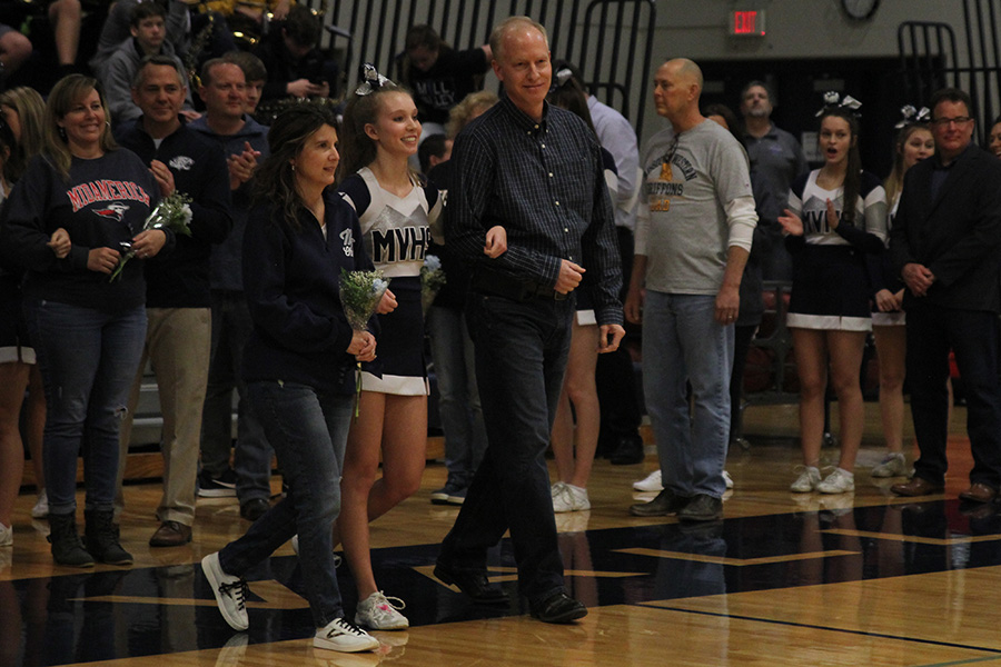 As+she+is+introduced+for+senior+night%2C+senior+Kate+Backes+walks+out+with+her+parents.