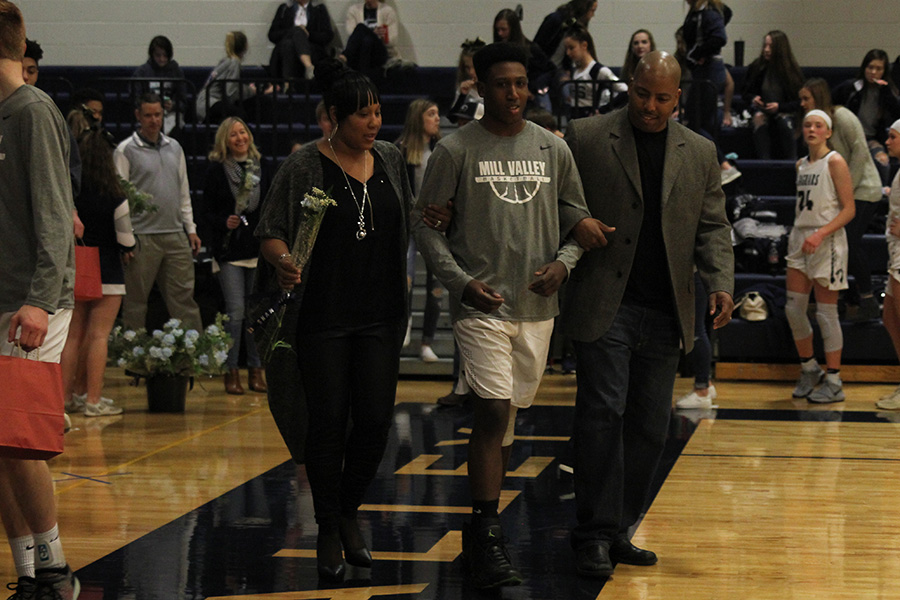 As+he+is+introduced+for+senior+night%2C+senior+Trey+Dameron+walks+out+with+his+parents.