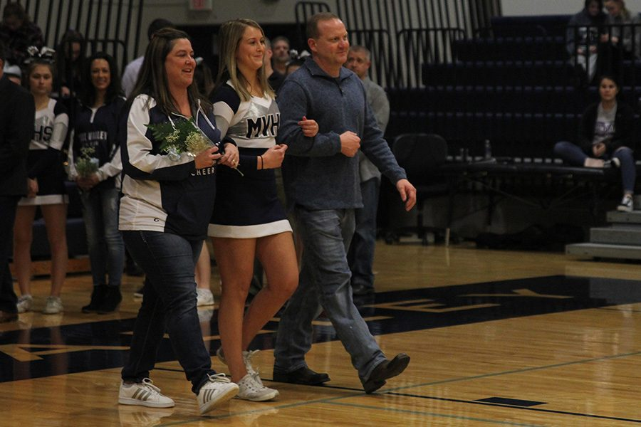 As she is introduced for senior night, senior Lexi Knappen walks out with her parents.