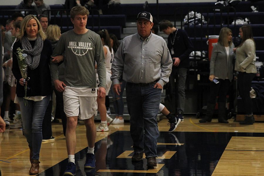 As he is introduced for senior night, senior Nick Davie walks out with his parents.