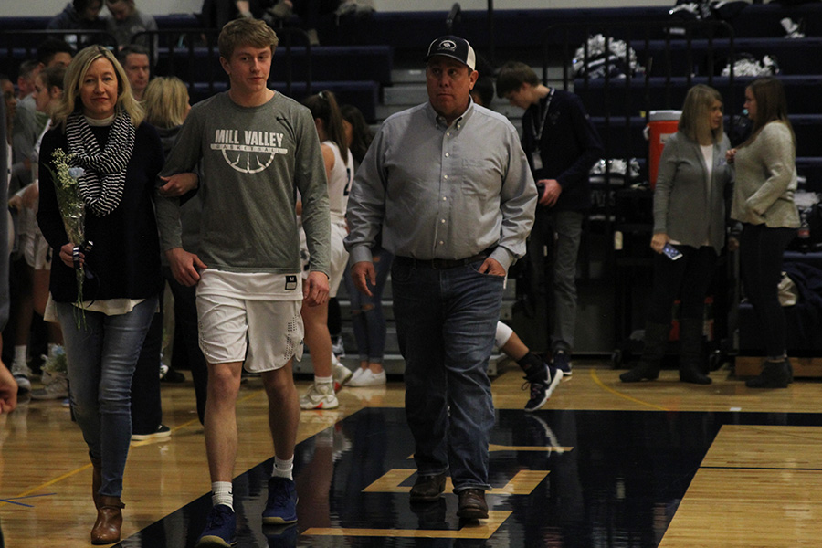 As+he+is+introduced+for+senior+night%2C+senior+Nick+Davie+walks+out+with+his+parents.