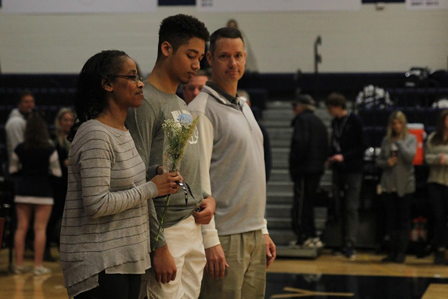 As he is introduced for senior night, senior Seth Hobson walks out with his parents.