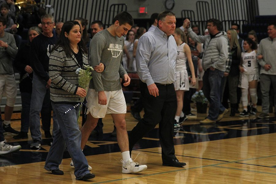 As he is introduced for senior night, senior James Smith walks out with his parents.