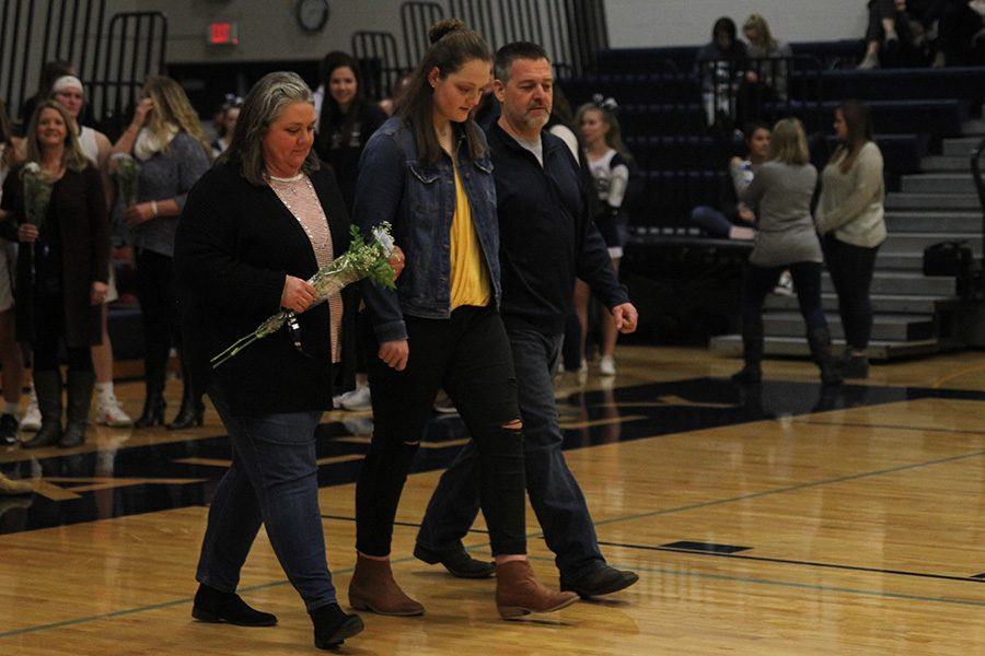 As she is introduced for senior night, senior Makayla King walks out with her parents.