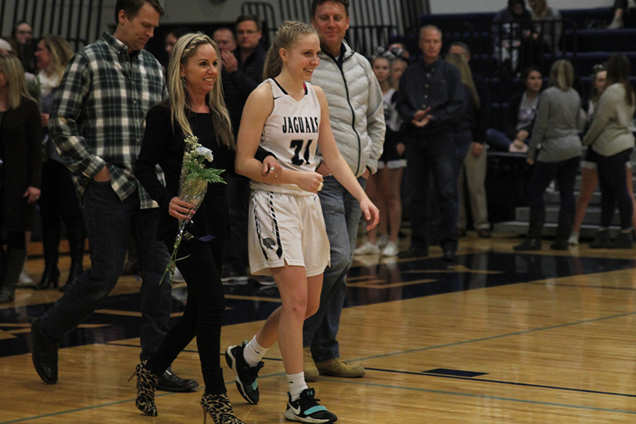 As+she+is+introduced+for+senior+night%2C+senior+Lexi+Ballard+walks+out+with+her+parents.
