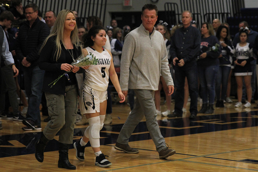 As+she+is+introduced+for+senior+night%2C+senior+Presley+Barton+walks+out+with+her+parents.