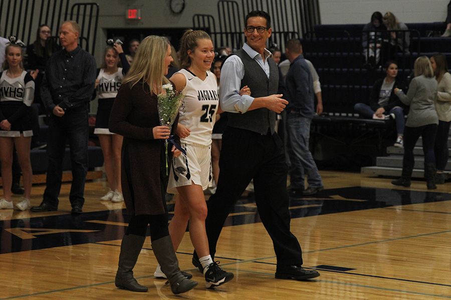 As+she+is+introduced+for+senior+night%2C+senior+Shyanne+Best+walks+out+with+her+parents.