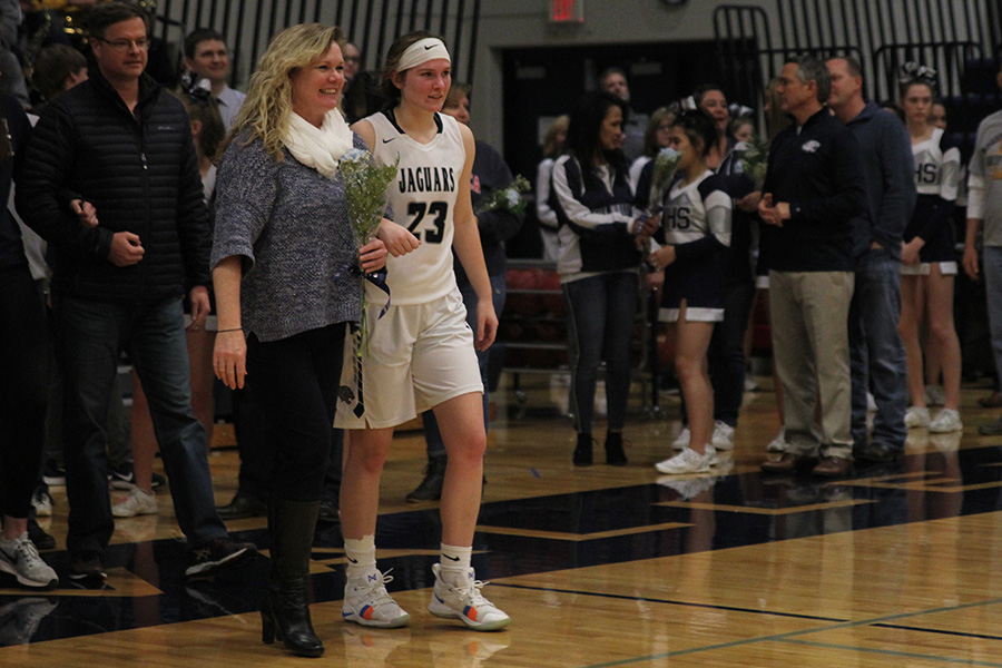 As+she+is+introduced+for+senior+night%2C+senior+Claire+Kaifes+walks+out+with+her+parents.