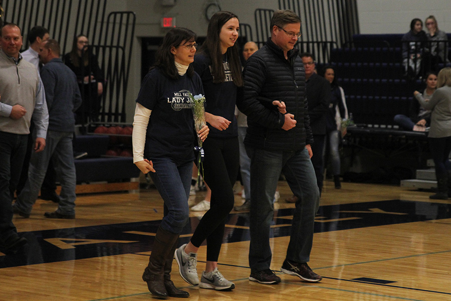 As+she+is+introduced+for+senior+night%2C+senior+Trinity+Knapp+walks+out+with+her+parents.