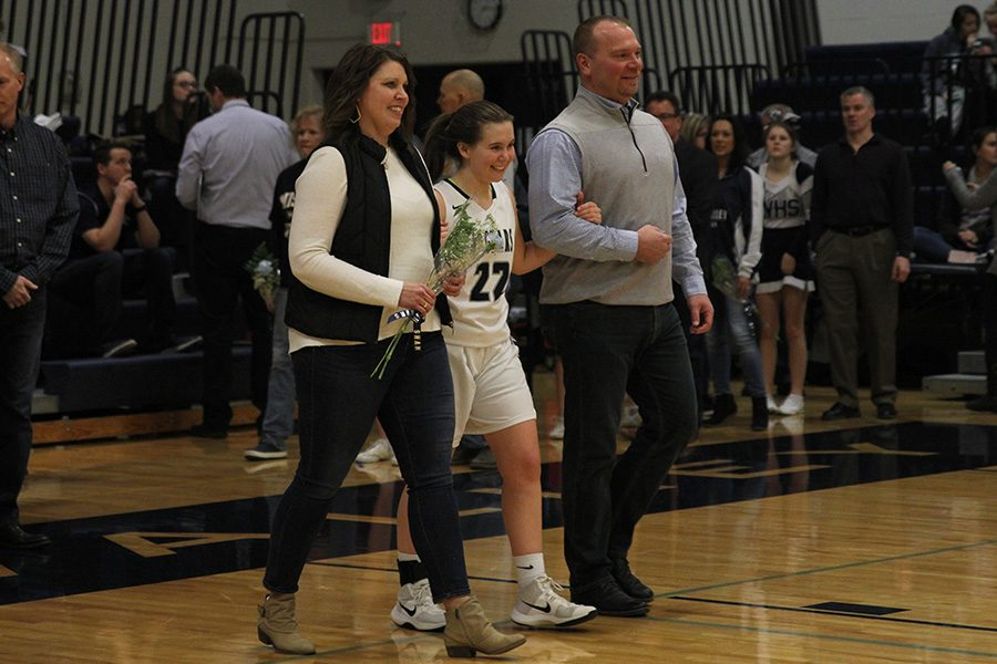 As she is introduced for senior night, senior Sydney Stuke walks out with her parents.