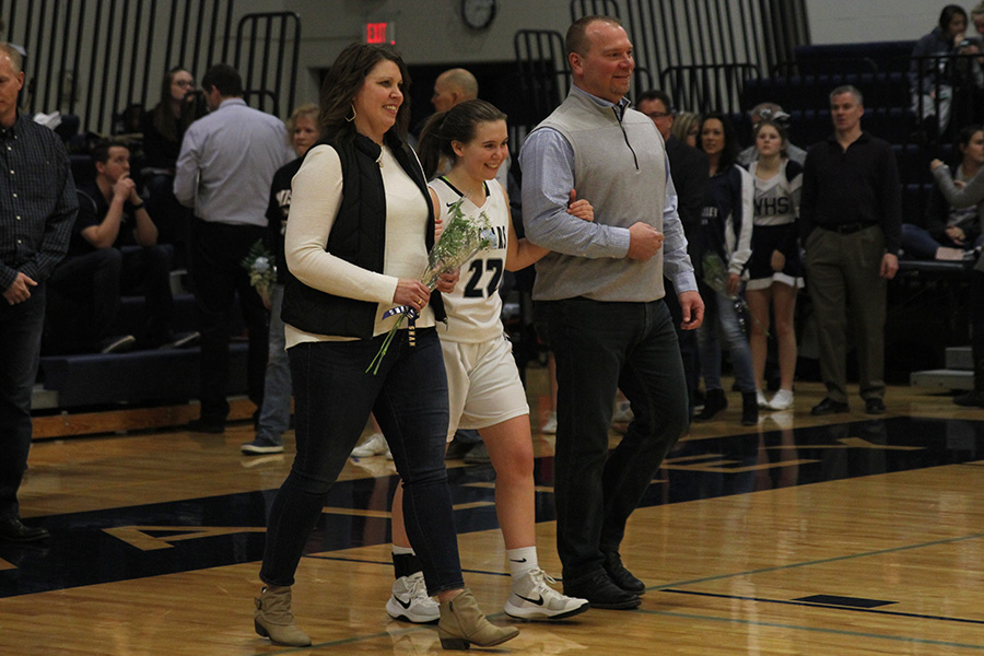 As+she+is+introduced+for+senior+night%2C+senior+Sydney+Stuke+walks+out+with+her+parents.