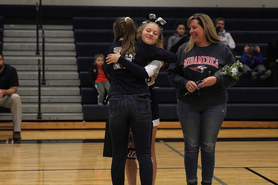 After she was introduced for senior night, senior Faith Dmyterko hugs a fellow cheerleader.