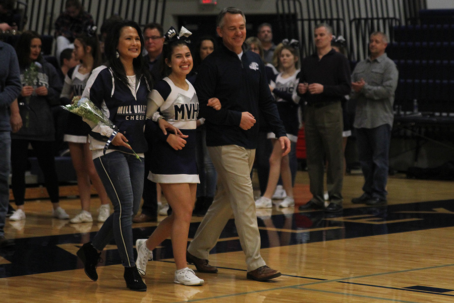 As+she+is+introduced+for+senior+night%2C+senior+Mya+Johnston+walks+out+with+her+parents.