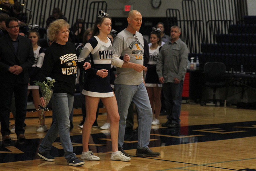 As+she+is+introduced+for+senior+night%2C+senior+Erin+Miller+walks+out+with+her+parents.
