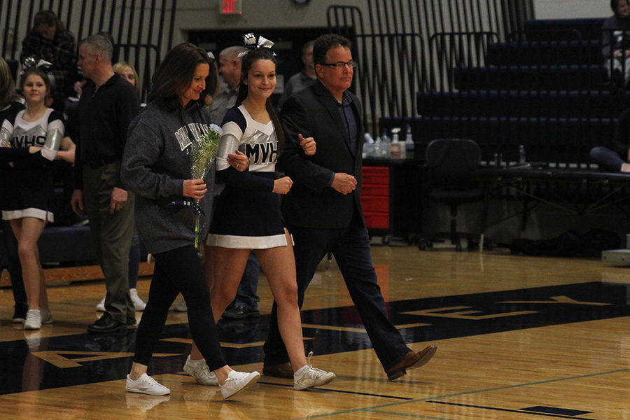 As+she+is+introduced+for+senior+night%2C+senior+Margaux+Porter+walks+out+with+her+parents.