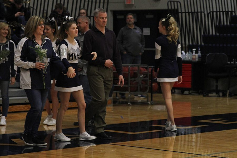 As she is introduced for senior night, senior Rielly Rittmann walks out with her parents.