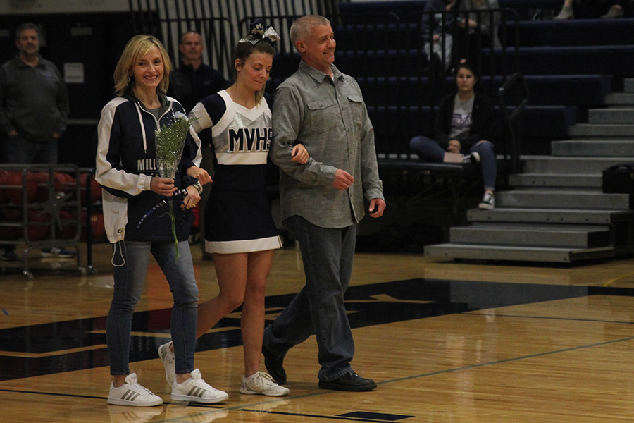 As+she+is+introduced+for+senior+night%2C+senior+Payton+Totzke+walks+out+with+her+parents.