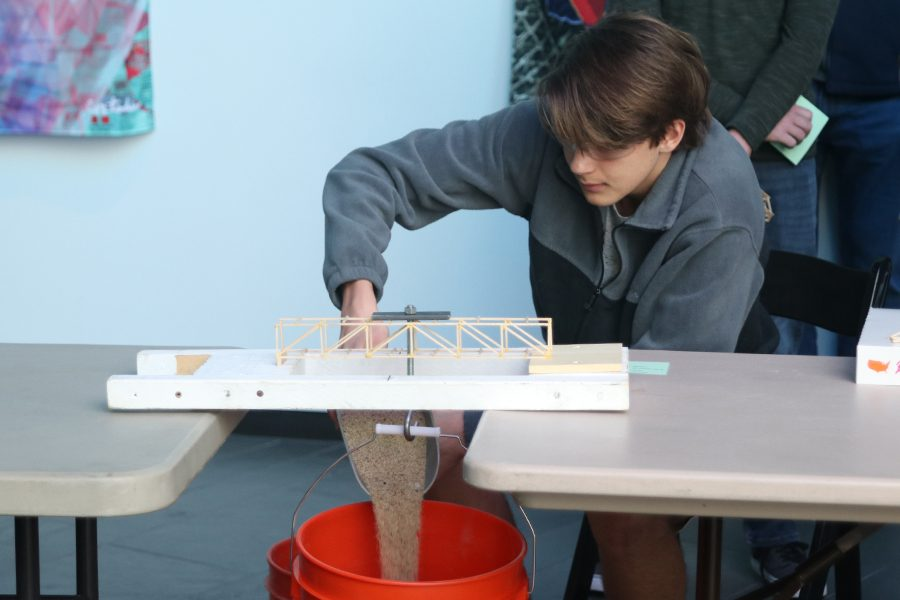 Quickly pouring sand, junior Nathan Greenfield tests how much weight his bridge can hold.