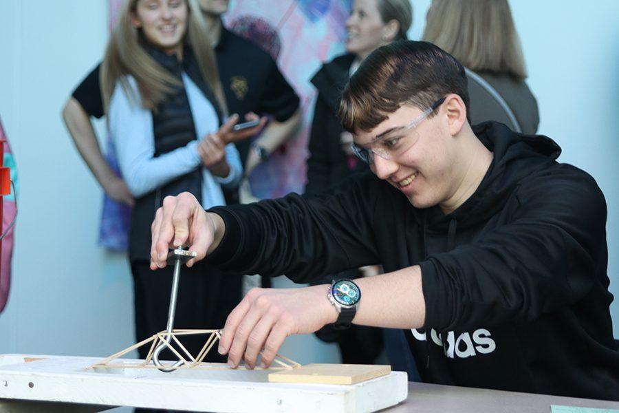 Attaching the hook to his bridge, senior Johannes Seberger prepares to test his bridge.