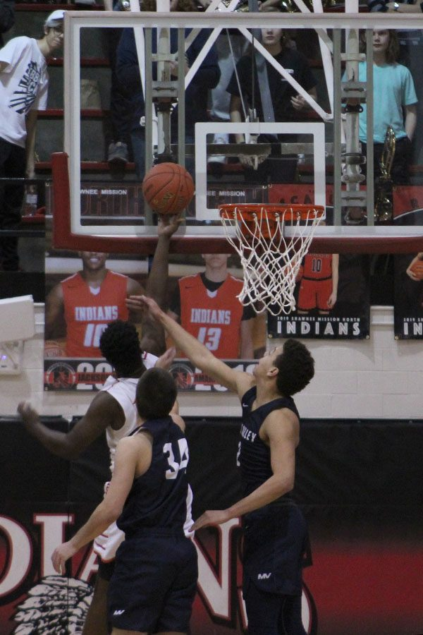 With their opponent at the rim, seniors Matty Wittenauer and James Smith try to block him.